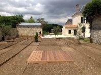 Le platelage en bois fait office de solarium dans le Jardin méditerranéen fraîchement semé